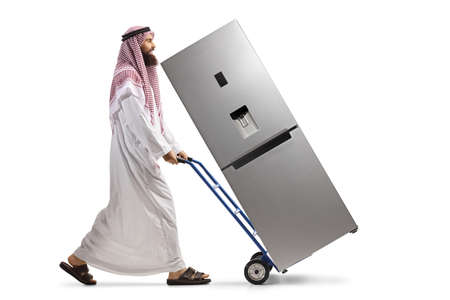 Photo pour Full length profile shot of a saudi arab man pushing a hand truck with a fridge isolated on white background - image libre de droit