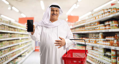 Photo pour Cheerful mature arab man with a shopping basket and a smartphone inside a supermarket - image libre de droit