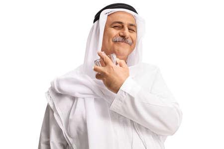 Photo pour Arab man in white dishdasha spraying a perfume isolated on white background - image libre de droit