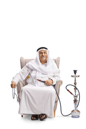 Photo pour Mature arab man sitting in an armchair with a shisha isolated on white background - image libre de droit