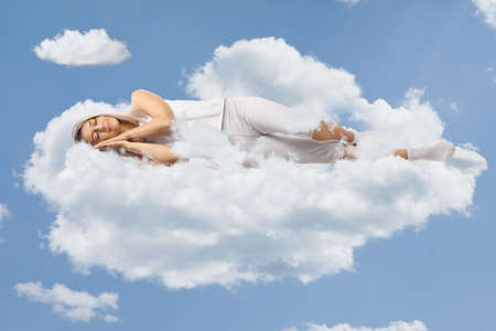 Photo pour Young woman in pajamas sleeping on clouds and blue sky - image libre de droit