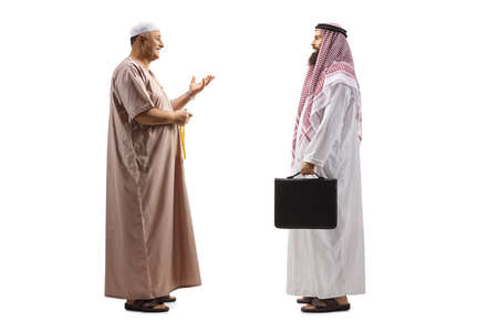 Photo pour Full length profile shot of a mullah talking to a saudi arab businessman isolated on white background - image libre de droit