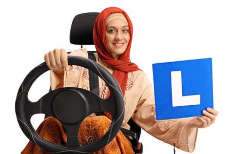 Photo pour Young muslim woman in a car seat holding a learner plate - image libre de droit