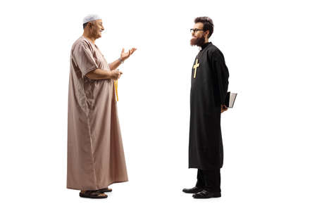 Photo pour Full length profile shot of a muslim man in traditional clothes talking to a christian priest - image libre de droit