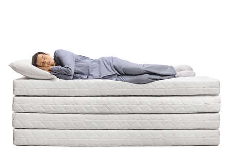 Photo pour Full length shot of a young man sleeping peacefully on  a pile of soft mattresses isolated on white background - image libre de droit