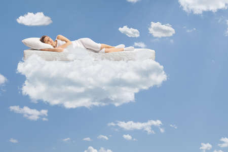 Photo pour Young woman sleeping on a floating mattress up in the clouds and a blue sky - image libre de droit