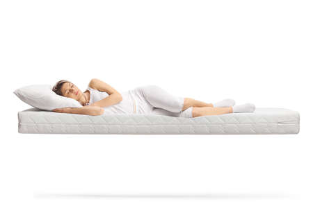 Photo pour Young woman in white pajamas sleeping on a floating mattress isolated on white background - image libre de droit
