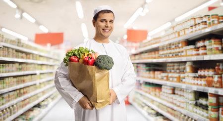 Photo pour Young muslim man holding a paper shopping bag with groceries inside a supermarket - image libre de droit