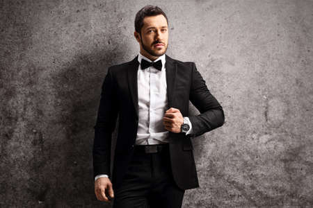 Photo pour Young man in a black suit and bow tie leaning on a rusty gray wall - image libre de droit