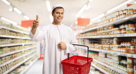 Photo pour Young man in ethnic clothes holding an empty shopping basket and gesturing a thumb up sign inside a supermarket - image libre de droit