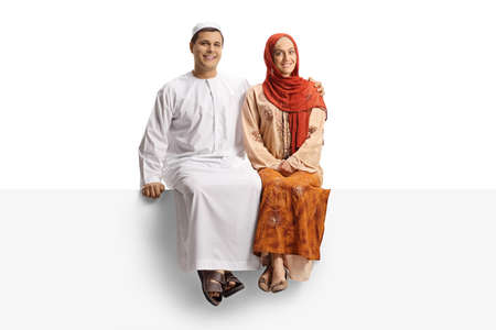 Photo pour Full length portrait of a young couple in ethnic wear sitting on a white panel isolated on white background - image libre de droit