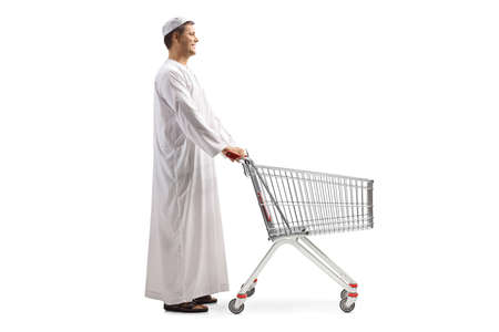Photo pour Full length profile shot of a man in ethnic clothes with an empty shopping trolley isolated on white background - image libre de droit