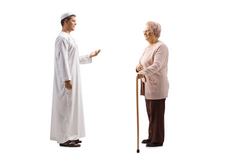 Photo pour Full length profile shot of a an elderly woman and a young man in ethnic clothes having a conversation isolated on white background - image libre de droit