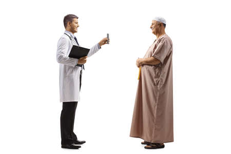 Photo pour Full length profile shot of doctor holding a smartphone and showing screen to an arab man conversation isolated on white background - image libre de droit