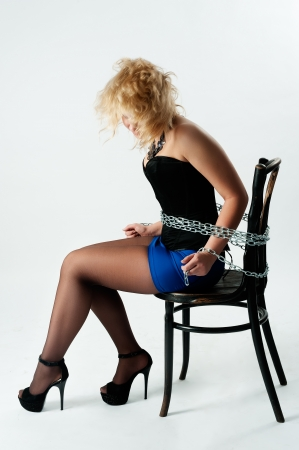 Attractive young woman tied up with chains  Isolated on white
