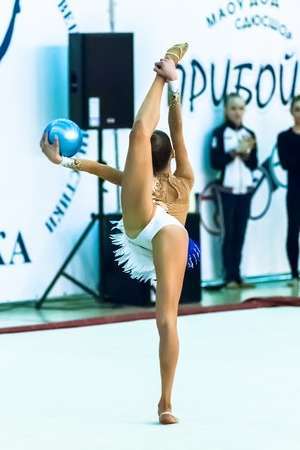 Tyumen, Russia - April 4, 2015: All-Russian competitions in rhythmic gymnastics \Spring grace\. Sports complex \Priboy\. Young attractive girl shows own skill in exercise with ball
