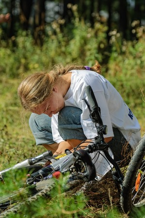 Vinzili, Russia - September 4, 2005: Velodanger competition in territory of unfinished psychiatric hospital. Woman repairing mountain bike