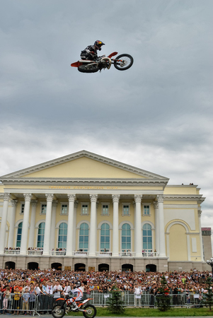 Tyumen, Russia - June 10, 2009: Red Bull X-Fighters Exhibition Tour. Freestyle Motocross. Motorcycle Jumping over city Drama theater background