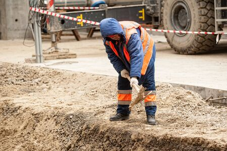 Photo pour Tobolsk, Russia - May 29. 2018: Sibur company. Construction of plant on processing of hydrocarbons. Worker with a shovel - image libre de droit