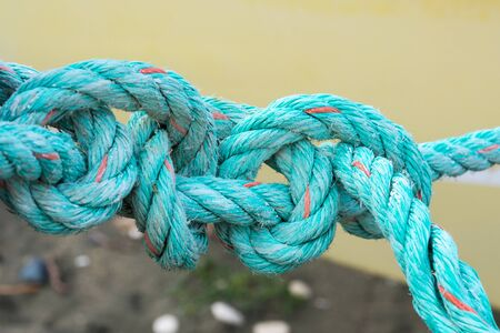 Photo pour Old green rope knotted on a yellow background. Knot. Insoluble problem concept - image libre de droit