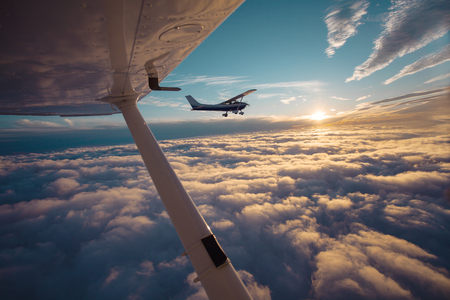 Photo pour Small single engine airplane flying in the gorgeous sunset sky through the sea of clouds - image libre de droit