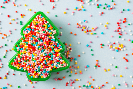 Photo for Flat lay view of Christmas tree shaped cookie cutter filled with rainbow sugar sprinkles. - Royalty Free Image