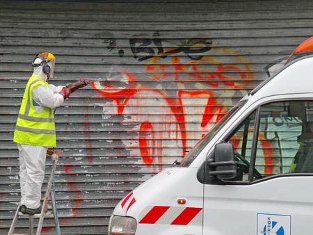PARIS, FRANCE - OCTOBER 2012: Man cleaning graffiti of a sprayed metal door in Paris, France.
