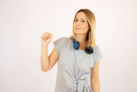 Photo pour Beautiful woman in grey dress with headphones - image libre de droit