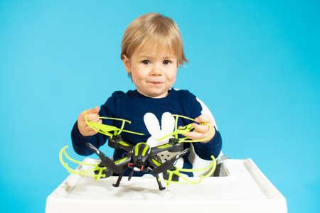 Foto de Baby boy sitting and holding a drone isolated over blue background. - Imagen libre de derechos