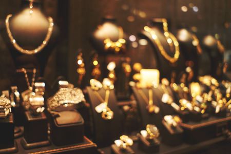 Blurred fashion boutique with jewelry made of precious metals. Store jewelry in silver and gold. Vetrin beautiful jewelry store. Blurred bokeh basic background for design