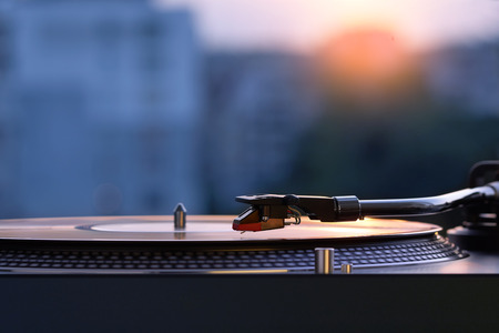Photo pour Turntable vinyl record player on the background of a sunset over the lights city. Sound technology for DJ to mix & play music. Black vinyl record. Vintage vinyl record player. Needle on a vinyl record - image libre de droit