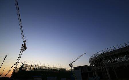 Photo pour Cranes at work, silhouetted on construction sites - image libre de droit