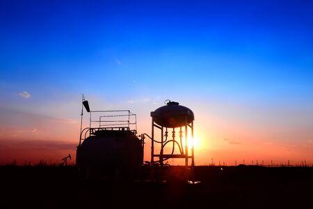 Photo pour Oil tanks, silhouetted against the setting sun - image libre de droit