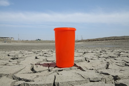 close up of red plastic cups in the dry land, creative images, urged people to conserve water because the water crisis is worsening, it will affect all our lives.