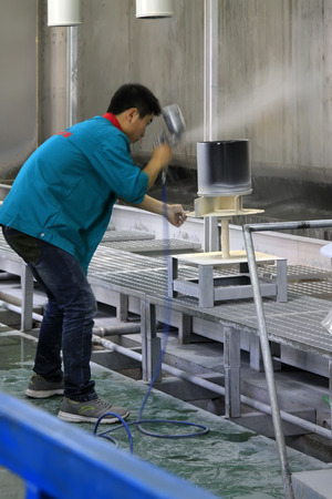 TANGSHAN CITY - MAY 29: Workers spray enamel glaze in a production workshop, on may 29, 2014, Tangshan city, Hebei Province, China