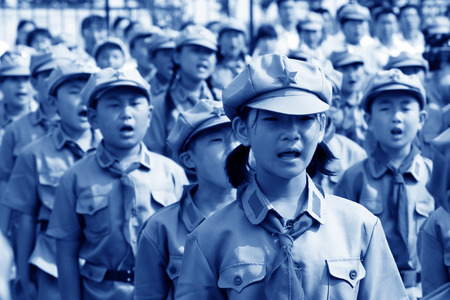 Elementary student dressed in blue military uniform and swear solemnly