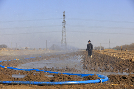 Luannan County - March 16, 2018: farmers are irrigating farmland, preparing farming, Luannan, Hebei, China