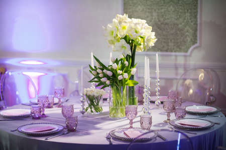 Photo pour decoration of a festive dinner with flowers of lilies and tulips on the wedding table in the interior of the restaurant. Decorated table for a celebration in purple tones. - image libre de droit