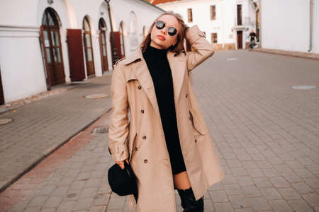 Photo for Stylish young woman in a beige coat and a black hat in his hands and glasses on a city street. Women's street fashion. Autumn clothing.Urban style - Royalty Free Image
