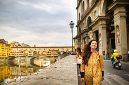 Foto de A tourist girl with an orange coat happily walks on the embankment in Florence, Italy. - Imagen libre de derechos
