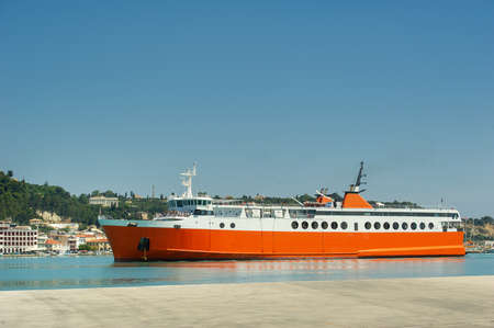 Photo pour Large red ferry for transporting cargo and people in the Mediterranean Sea near the Greek island promenade, Greece. - image libre de droit