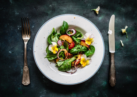 Photo for Coloful summer salad with nectarines and edible flowers. Top view. - Royalty Free Image