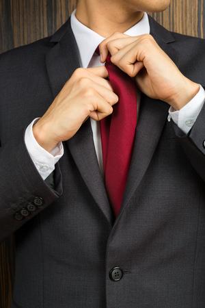 Photo pour Asian man in a suit correcting his red necktie - image libre de droit