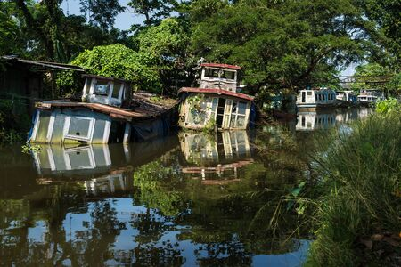 Photo pour Sunken house boats with reflections in the water in Kerala backwater canal, Allappuzha, Alleppey, India - image libre de droit