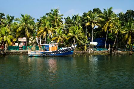 Photo pour Ocean fishing boat along the canal Kerala backwaters shore with palm trees at a sunny day between Alappuzha and Kollam, India - image libre de droit