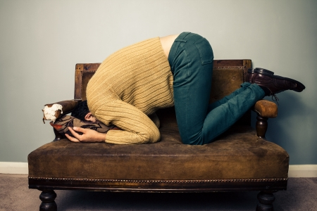 Photo pour Young man burrying his face in cushion on vintage sofa - image libre de droit