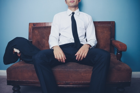 Young businessman is relaxing on a vintage sofa after work