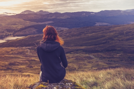 Young woman is sitting on top of mountain admiring the sunset