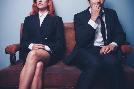 Photo pour Confident businesswoman sitting next to nervous businessman - image libre de droit