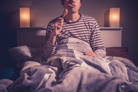 Young man eating chicken in bed